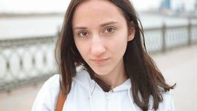 一名年轻不快乐的白种人妇女的特写镜头画象在一座桥梁前面的在河附近 愉快的少妇在河边 股票视频
