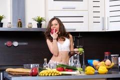 一名年轻亭亭玉立的妇女的画象女用贴身内衣裤的在厨房里 图库摄影