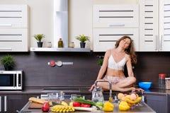 一名年轻亭亭玉立的妇女的画象女用贴身内衣裤的在厨房里 免版税图库摄影