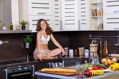 一名年轻亭亭玉立的妇女的画象女用贴身内衣裤的在厨房里 库存图片