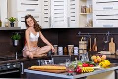 一名年轻亭亭玉立的妇女的画象女用贴身内衣裤的在厨房里 免版税库存图片