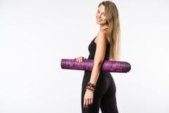 一名年轻健身妇女的后面看法画象有瑜伽席子的在白色背景 库存图片