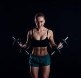 一名年轻健身妇女的画象做与哑铃的运动服的锻炼在黑背景 被晒黑的性感的运动女孩 库存图片