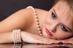 一名年轻可爱的妇女的面孔有珍珠项链的 免版税库存图片