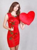 一名年轻可爱的妇女的画象有一个心形的枕头的 免版税库存照片