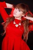 一名年轻可爱的妇女的画象有一根红色头发的在一红色ev 库存图片