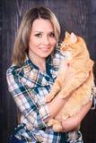 一名年轻可爱的妇女的画象有猫的在手上 库存照片