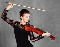 一名年轻可爱的小提琴手妇女的画象一黑evenin的 库存照片