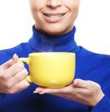 拿着杯子的一名年轻和愉快的妇女的画象 免版税库存图片