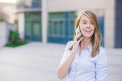 一名年轻女实业家谈话在她的电话,当站立在办公大楼前面时 免版税图库摄影