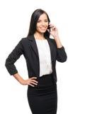 一名年轻女实业家谈话在白色的电话 免版税库存图片