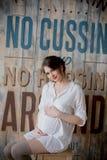 一名年轻孕妇的画象白色衬衣的在照片演播室 图库摄影