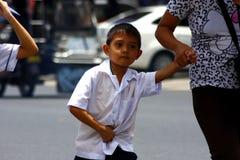 一名年轻学生走与他的上学的母亲 免版税库存照片