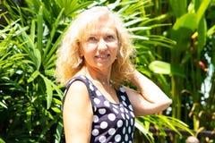 一名50岁的妇女的画象在反对绿色热带棕榈树背景的夏天  库存图片