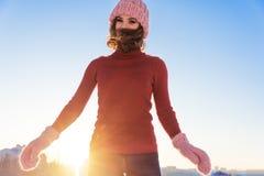 一名年轻微笑的妇女的冬天画象一桃红色帽子和mitte的 库存照片
