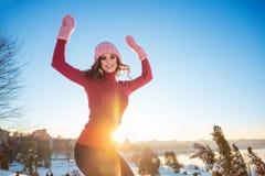 一名年轻微笑的妇女的冬天画象一桃红色帽子和mitte的 免版税库存照片