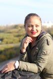 一名年轻快乐的胖的妇女的画象雨衣的在街道上在秋天 库存图片