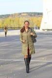 一名年轻快乐的胖的妇女的画象雨衣的在街道上在秋天 免版税库存照片