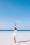 一名年轻欧洲长的头发妇女在一个白色沙滩站立在海洋旁边 一件白色礼服的一个女孩拿着一个菠萝 库存图片