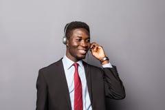 一名年轻男性客户服务代表或电话中心工作者或者操作员,支撑杆的特写镜头画象讲话与他 库存照片