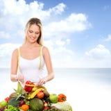 一名年轻白肤金发的妇女和堆新鲜水果 库存照片