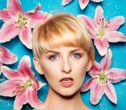 一名年轻白肤金发的妇女的头有花的在边 免版税库存图片