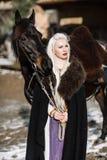 一名年轻白肤金发的妇女的画象一个黑斗篷的有马的 免版税库存照片