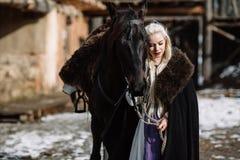 一名年轻白肤金发的妇女的画象一个黑斗篷的有马的 免版税库存图片