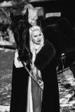 一名年轻白肤金发的妇女的画象一个黑斗篷的有马的 库存图片