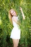 一名年轻白肤金发的妇女的画象绿色柳树的 免版税图库摄影