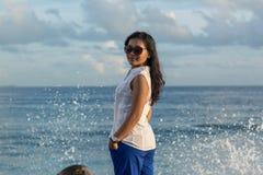 一名年轻美丽的亚裔妇女的画象回顾与后边波浪飞溅的太阳镜的 免版税库存图片