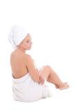 一名年轻美丽的妇女的后面看法毛巾的坐白色 免版税图库摄影