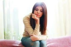 一名年轻美丽的沉思妇女的画象坐沙发 免版税库存照片