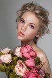 一名年轻美丽的白肤金发的妇女的画象特写镜头有鲜花的 免版税库存图片
