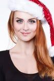 一名年轻美丽的红发妇女的画象一个发光的圣诞节帽子的,她使用与蓬松白色大型机关炮 库存图片