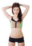 一名年轻美丽的运动的妇女佩带的体育短裤和上面的演播室画象 图库摄影