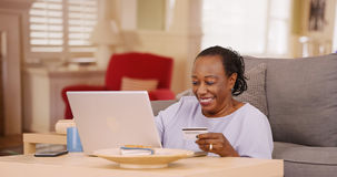 一名更老的非裔美国人的妇女使用她的信用卡和膝上型计算机做一些网上购物 库存图片