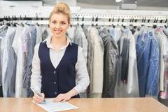一名洗衣店工作者的画象衣物的背景的在挂衣架的 免版税库存图片
