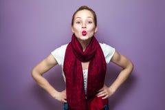 一名年轻逗人喜爱的妇女的画象有红色围巾和雀斑的在她的面孔吹的亲吻和看在紫色背景的照相机 免版税库存照片