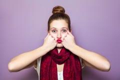 一名年轻逗人喜爱的妇女的画象有红色围巾和雀斑的在她的面孔吹的亲吻和看在紫色背景的照相机 库存照片