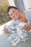 一名年长妇女在一t的衡量单位保留很多钞票 库存图片