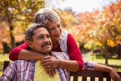 一名年长妇女拥抱她的丈夫坐长凳 图库摄影