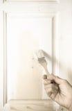 一名年长妇女的手有一支画笔的与白色油漆doo 库存图片