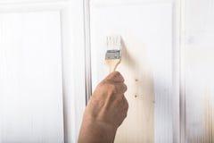 一名年长妇女的手有一支画笔的与白色油漆doo 免版税图库摄影