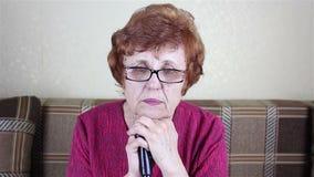 一名年长带眼镜妇女的画象 倾斜在一拐棍的Sits 影视素材