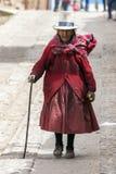 一名年长秘鲁妇女步行沿着向下一条街道在Maras镇在秘鲁 图库摄影