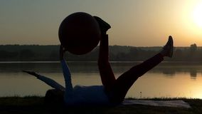 一名slportive妇女在有一fitball的一张席子说谎在手上在日落 股票视频