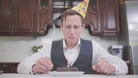 一哀伤的年轻人的被弄脏的画象吹灭在一个小巧克力蛋糕的生日帽子的蜡烛在厨房里 ?treadled 股票视频