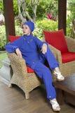 一回教游泳衣burkini的可爱的妇女在一把leteny椅子在庭院里 免版税库存照片