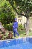 一回教游泳衣burkini的可爱的妇女在水池边在一个热带庭院里 免版税库存照片